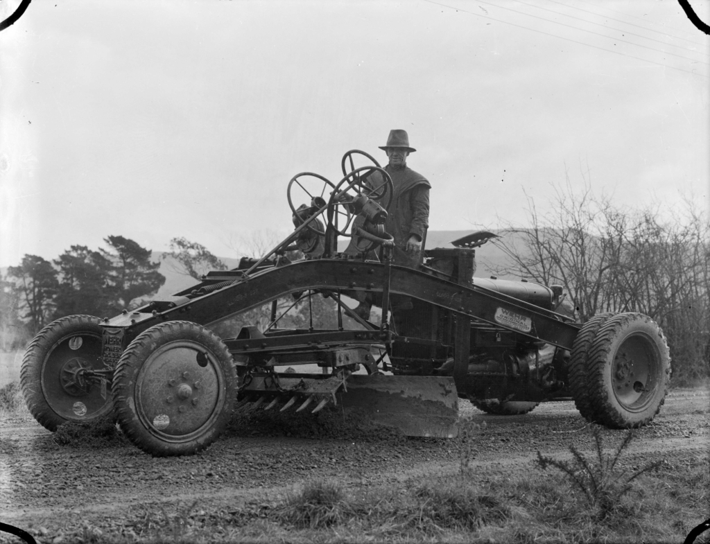 1024px-A_grader_working_on_the_road_at_Upper_Hutt,_1936_ATLIB_306472-1